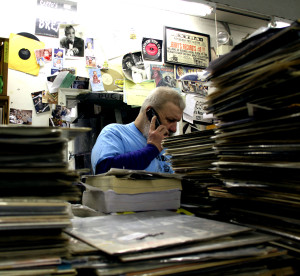 Jerry answers the phone amid stacks upon stacks of records and memorabilia. Photo by Kate Dillon