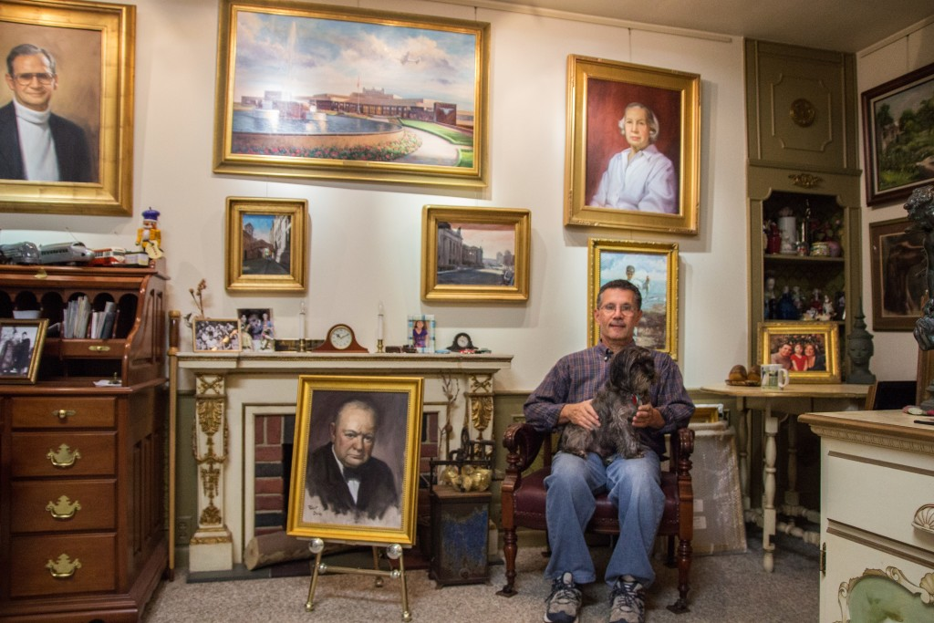 Robert Daley, owner of South Hills Art Studio, poses in front of some of his many paintings. Photo by Claire Murray.