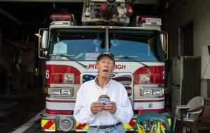 George shows off his numerous patches in front of one of Brookline's fire trucks at the firehouse. Photo by Joseph Guzy.
