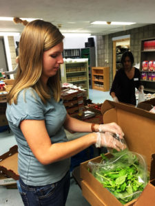 Lydia Strickling, a junior at Duquesne University and volunteer at the pantry, sorts fresh basil for distribution to community members.
