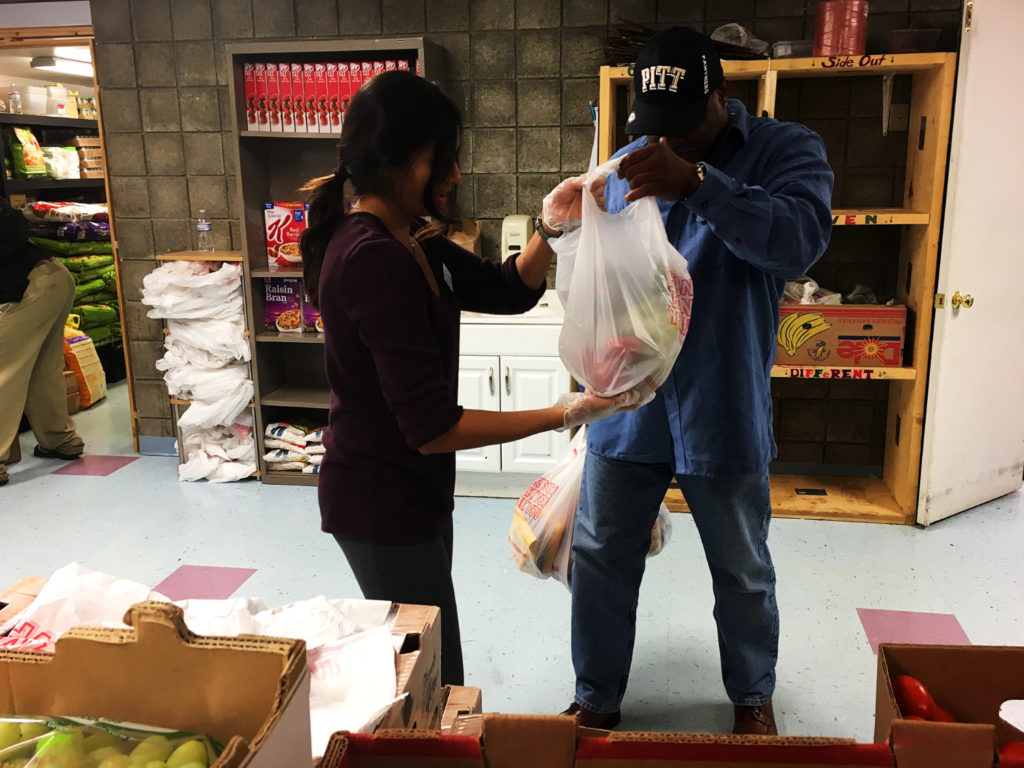 Volunteer Divya Patel, a pharmacy student at the University of Pittsburgh, hands bags of fresh produce to local patron Wayne Young.