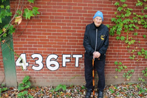 Phil Coyne stands in front of the remaining traces of Forbes Field in Oakland, a portion of the stadium's outfield wall.