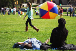 Pitt students Minah Chapell (left) and Ayesha Sesay (right) lounge on the Plaza's lawn.